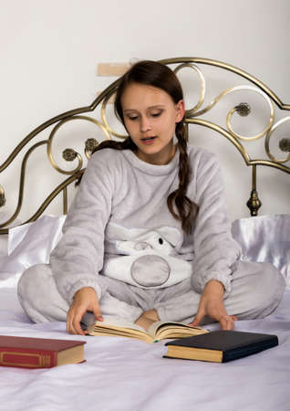 young student girl reads a book while lying on a bed doing homework
