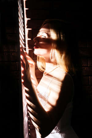 Beautiful woman in underwear stending near window and closed louver on a sunny day. Striped shadow on a body