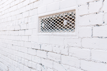 Perspective view of an old cracked white brick wall with grate in an alley.