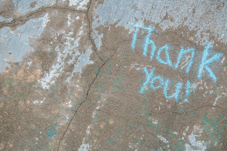 Old distressed cracked concrete wall with thank you written diagonally across the corner with blue chalk.