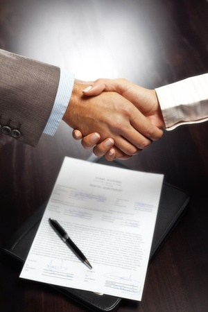 contract signing: Handshake above signed contract