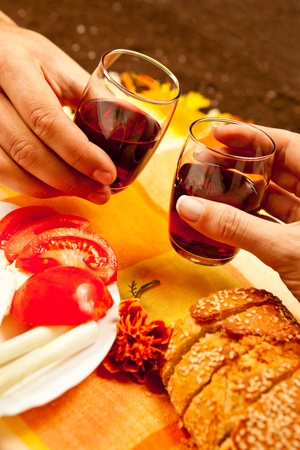 Romantic lunch setting for two with red wine, fresh vegetables and bread photo