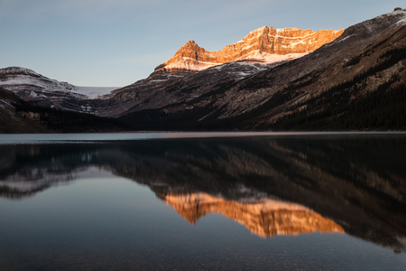 Canadian Rockies light up at sunrise, reflected in Bow Lake, Banff National Park