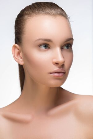 Glamour portrait of beautiful woman model with fresh daily makeup and romantic wavy hairstyle. Fashion shiny highlighter on skin, sexy gloss lips make-up and eyebrows