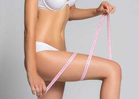 elasticidad: Mujer de adelgazamiento que mide su cuerpo sobre fondo blanco