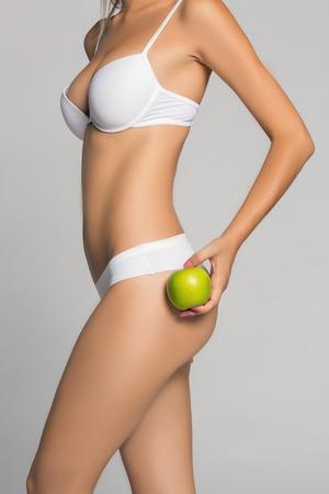60510370 - Retrato de la hermosa mujer joven en ropa interior blanca que  sostiene la manzana verde. 7dcb97034a1e