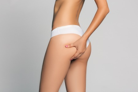 supple: Young woman is touching her skin on buttock to check its supple. Isolated on white.