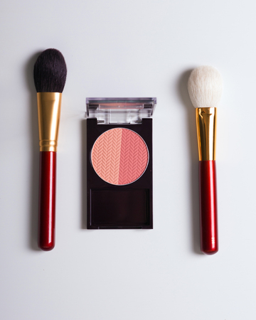 perfumery concept: Golden cosmetics - powder, blusher, brush on light wooden background with copy space. flat lay.