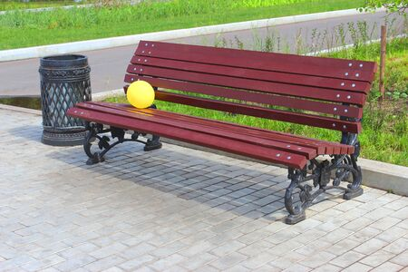 Childrens yellow balloon on a wooden bench in the park. photo
