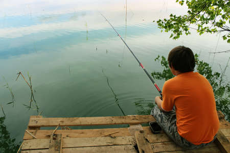 A boy sitting on the dock to fish on the bait float on the lake in summer. photo