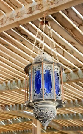 Dusty old street lamp in Arabic style, hanging from the ceiling under a wooden canopy. photo