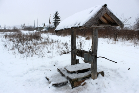 Rural landscape with a view of the street in a village in the winter and well with drinking water. photo