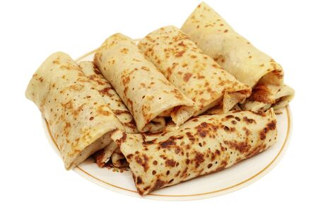 fillings: Russian pancakes with fillings wrapped up in them, stacked on a plate, isolated on white background.