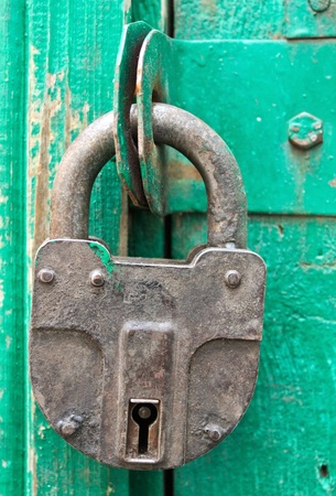 Padlock hanging on a wooden barn door photo