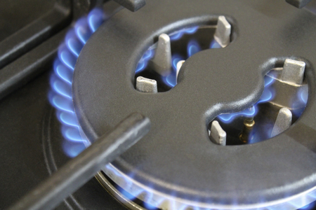 Burning blue flame gas burners cooktop closeup photo