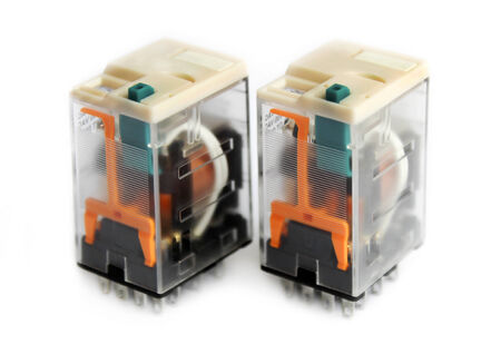 catena: Two miniature relays in transparent plastic cases isolated on white background