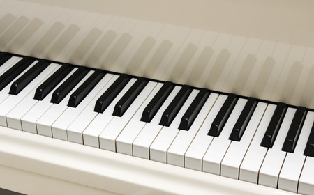 Open white grand piano keyboard close up photo