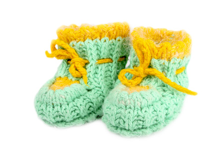 fraternal: Baby woolen booties, knitted of green and yellow thread