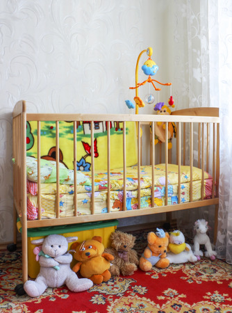 Baby crib in the children's room with toys