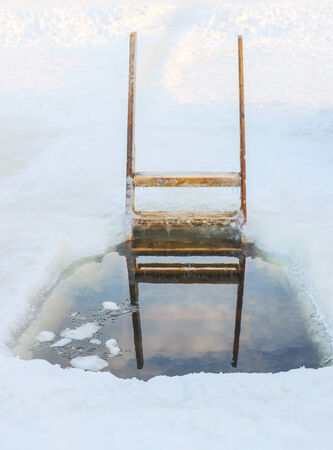 baptizing: Epiphany hole with a wooden staircase for winter swimming in the river