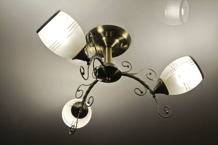 enable: Beautiful bronze chandelier with three shades of white frosted glass Stock Photo
