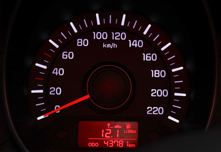 Car speedometer dial with red backlit close-up