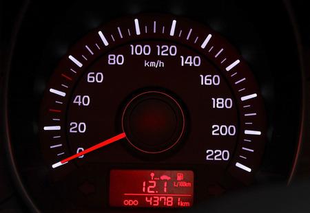 velocímetro: dial del velocímetro del coche con la luz de fondo rojo de cerca