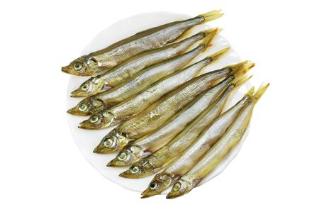 carcinogen: Smoked capelin on a white plate close-up isolated