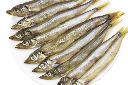 Smoked capelin on a white plate close-up isolated
