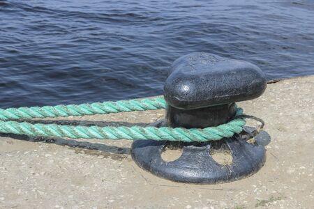 mooring bollard: Rope from a ship on a black mooring bollard