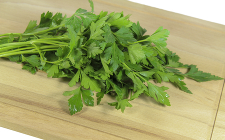 potherb: Bunch of parsley on a cutting board Stock Photo