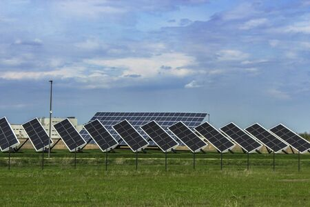 A series of solar panels against a background of green grass and sky with clouds