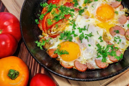 Scrambled eggs with tomatoes, sausages, sweet pepper and sprinkled with chopped parsley in a frying pan Stock Photo