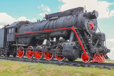 Old Soviet locomotive standing on the siding Stock Photo