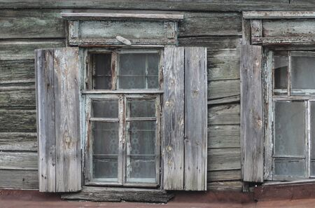 Windows of an old wooden house with shutters
