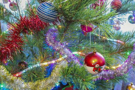 Colorful toys and a garland on a Christmas tree closeup