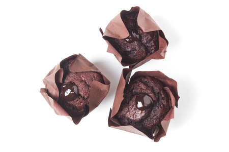 Chocolate muffins in a paper wrapper isolated on a white background. View from above