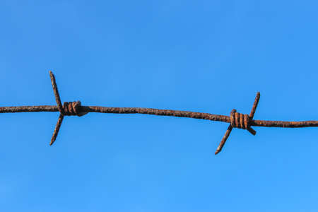 Fragment of old rusty barbed wire on blue sky background 版權商用圖片