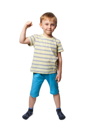 A boy in blue shorts and a yellow striped t-shirt shows his biceps