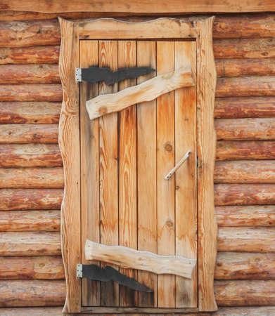 Wooden front door to a rustic log hut