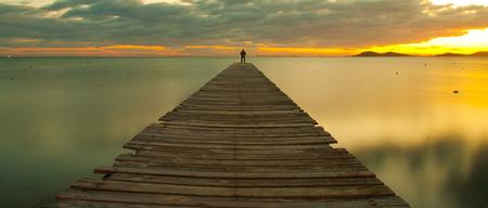 man on jetty at sunrise Stock Photo