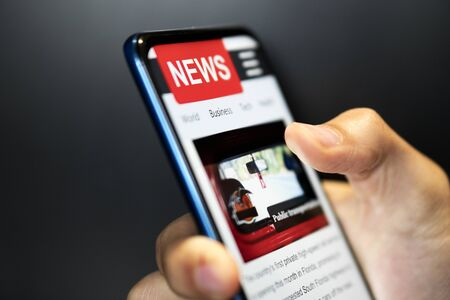 A man holding mobile smart phone with news on screen. Newspaper online portal in browser. Reklamní fotografie