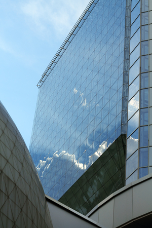 Clouds reflected in the glass building on a sunny day