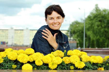 median age: Woman at the flower beds with yellow flowers