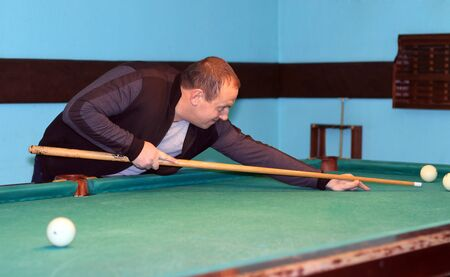 a man with a cue plays billiards