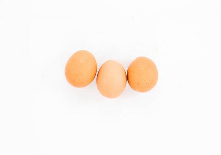 ova: three brown eggs over white  Stock Photo
