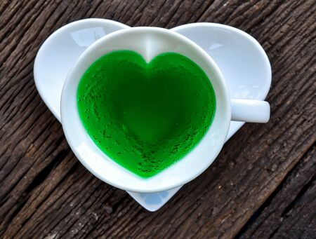 chlorophyll: chlorophyll in cup shape of heart on a wooden table old.