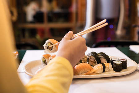 Sushi Japanese food close-up with woman hand in a restaurant. Lifestyle sashimi tasty seafood and rice rolls. Yellow color of the year