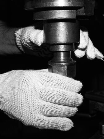 workpiece: Hands of the master - the versatile busy configuring the machine for the grooves of the workpiece. Stock Photo