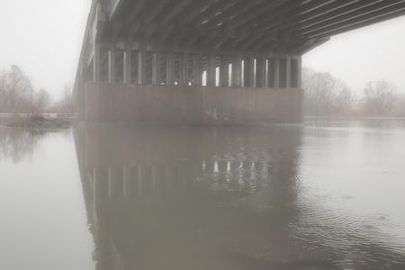 Spring mist under the bridge Фото со стока